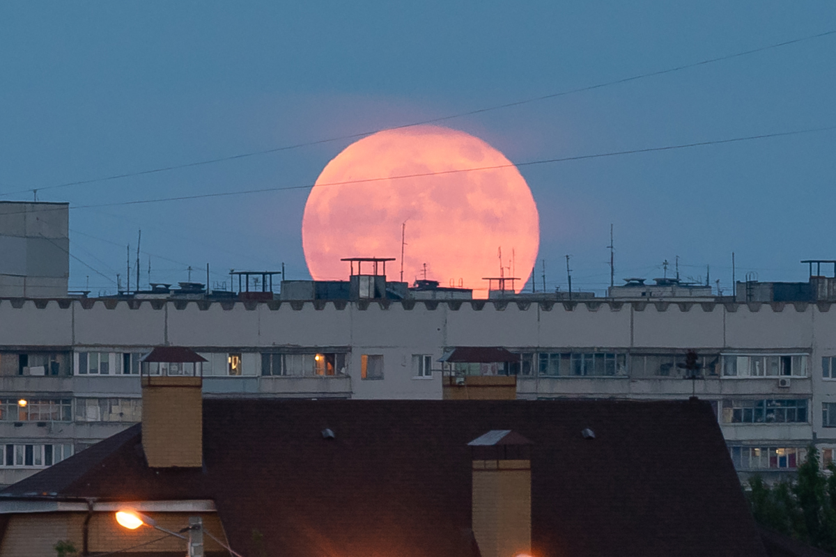 Восход полной луны над крышей дома в Харькове